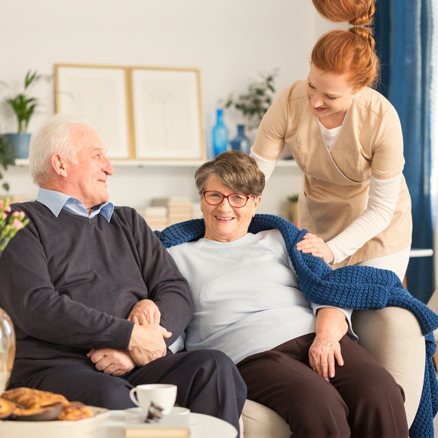 caregiver taking care of two senior people