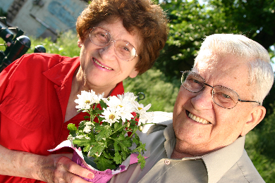senior man and woman holding a bouquet
